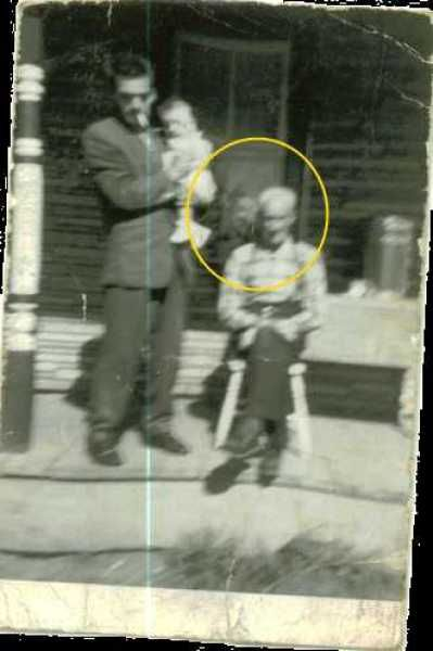 Here is an old photo of a man holding his daughter, while his father sits in front of their porch. It seemed like a pretty normal day, that ...