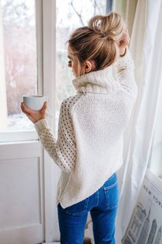 Top knot + ivory turtleneck sweater.