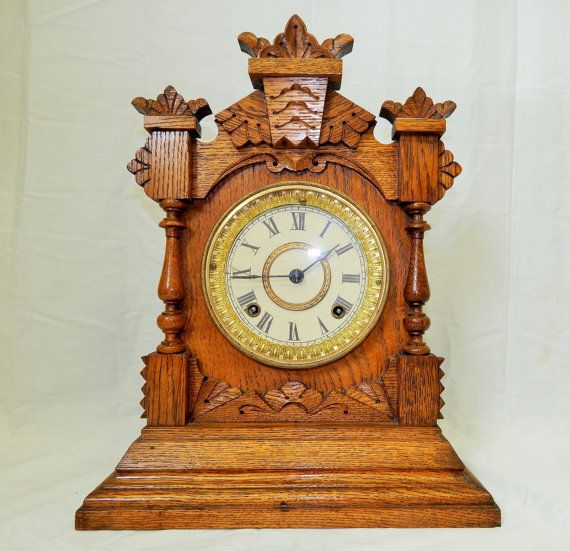 """13.) Antique Ansonia """"Tivoli"""" Carved Oak Kitchen/Mantel Clock-Excellent, Fully Working Condition with Key and Pendulum! Circa 1882. This is a beautiful example of the pressed or carved oak kitchen clocks that were heavily sought after in the late 1800s-early 1900s. Each clock was made from carved or pressed oak in a variety of gorgeous finishes and unique themes. This particular clock boasts a gorgeous light and natural finish that stands out beautifully with the gold ornate around dial. The…"""