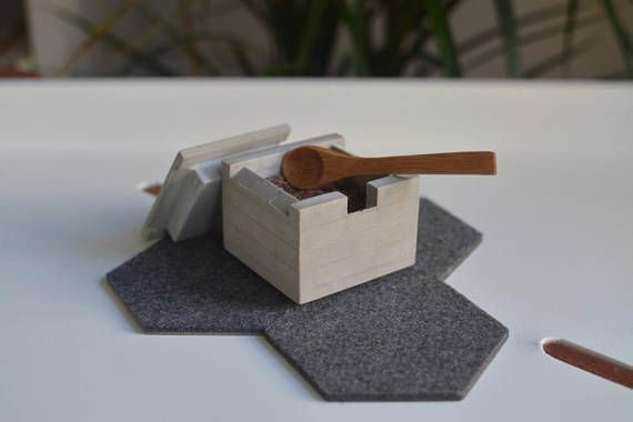 This finely detailed, architecture inspired salt cellar is hand cast from a mixture of portland cement and marble dust. Each salt cellar is unique, as they are individually cast and hand finished. A small bamboo spoon is included with every purchase. Dimensions 2.5 x 2.5 x 2