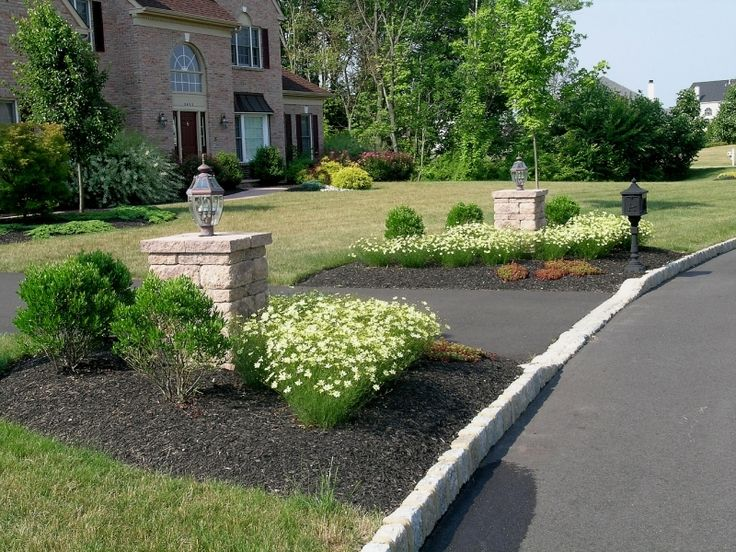 The landscaping surrounding the pillars at the driveway entrance
