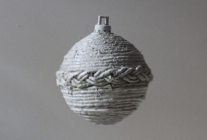 The ball wrapped with cord and braids coloured in white.