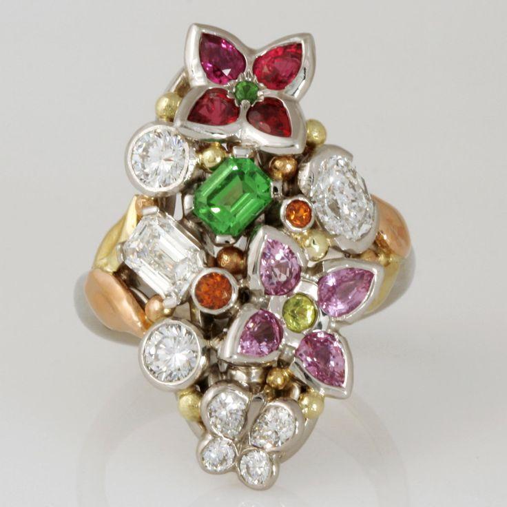 Handmade 'Dance of life'. Palladium, 18ct green gold and 18ct rose gold ring featuring diamonds, emeralds, tsavorite garnets, rubies, pink sapphires, greenish yellow chrysoberyl and spessartite garnets.