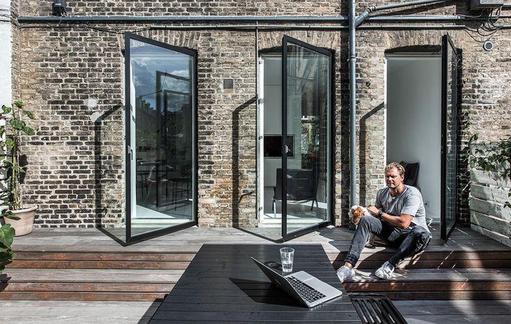 """<p class=""""bodytext"""">Tre glasvinduer/døre med sorte rammer på række forbinder husets baghave og k..."""