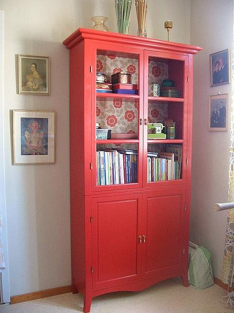 Love this reddish coral display cabinet and the pretty flower papered back...