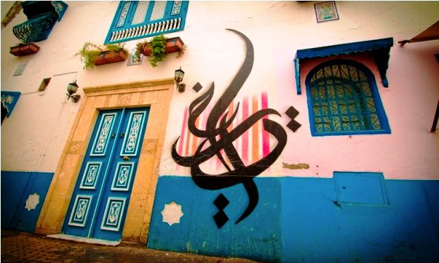 "eL Seed French-Tunisian street artist eL Seed has a unique style which he's coined as ""calligraffiti,"" the combination of calligraphy and graffiti"