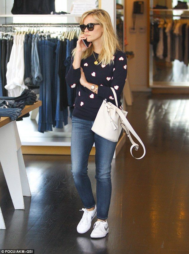 Hearts afire: #Reese stood out in a cute navy blue sweater covered in white hearts along with blue jeans and Nike sneakers.Oscar therapy