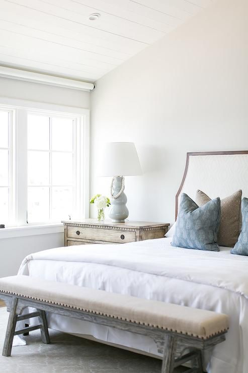You'll feel at ease in this beautiful cottage bedroom featuring a gray wash sawhorse bench placed on a gray rug in front of a bed covered in white bedding topped with blue paisley block print and brown pillows placed in front of a wood and fabric curved headboard.