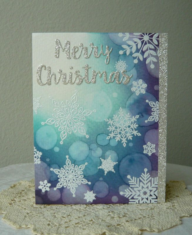 Hand-stamped Christmas card, featuring beautiful snowflakes on purple and green watercolor background.