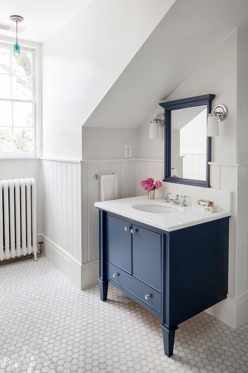 Exquisite bathroom features white paint on upper walls and beadboard trim on lower walls lined ...