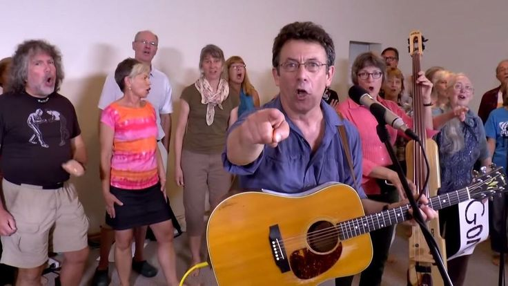 """Tony Turner wrote and sang """"Harperman,"""" leading a (barefooted) choir through lyrics that ask questions such as """"Who squashes all dissent?"""" and """"Who muzzles all the scientists?"""""""