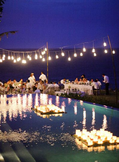"""Waterside dinner at night; love the simple hanging lights and the """"rafts"""" of floating candles in the pool.  Could also be really cool.  Could even use the battery operated ones so they don't flicker out..."""