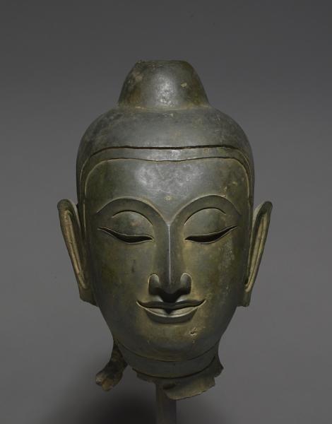 Tête de Buddha Thailande Style dit de Phitsanulok ca 15°-16° siècle Alliage cuivreux. H. 29,5 cm Superbe tête de Buddha aux traits fins et réguliers, et à l'expression empreinte de sérénité. On noter le très beau minimalisme exprimé dans le traitement allant jusqu'à choisir de ne pas figurer les boucles de la chevelure sur la tête et l' usnîsa. On notera l'urna simplement indiquée sur le front au dessus de la jointure des sourcils. Très belle patine oxydée.