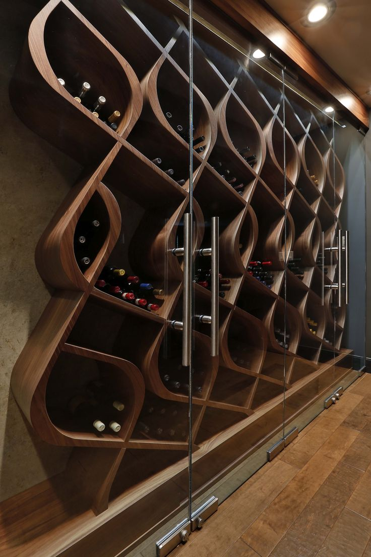 Unique wine storage designed and built by Genuwine Cellars. This wine cellar style is known as the Q Curve and holds approximately 380 bottles within curved wood wine racks. This one-of-a-kind Architectural Series wine wall concept features a precision-crafted set of glass doors that encloses a completely custom curved walnut rack. LED strip lighting recessed into both the base and bulkhead illuminates the cabinet and adds a futuristic touch to this modernist design.