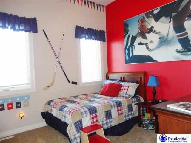 Hockey themed boys bedroom with red accent wall.
