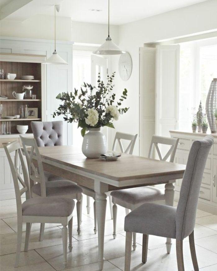 deco campagne chic dans la salle a manger table en bois chaises en bois blanches avec revetement gris vase de fleurs vaisselier blanc suspensions