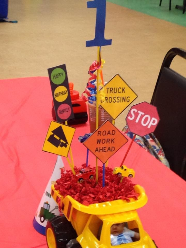 Truck centerpieces. Created road signs on computer & Printed road signs & glued onto colored sticks, glued foam block in dump truck to hold road signs, put red confetti on top of foam to hide foam. Put birthday boy picture in cab of truck as the driver. Staying with colors of themed party. Bought trucks & confetti on clearance after xmas, foam from dollar store, painted skews