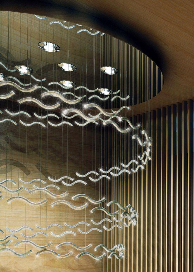 Modern chandelier made of glass tubes filled with crystals hanging on sparkling fiber optics. Detail.