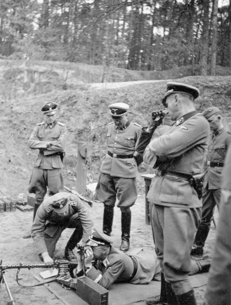 """Reichsführer SS Heinrich Himmler tests a MG 34 machine gun.First on the left is his adjutant, Cpt Joachim Peiper, who was to become one of the most decorated Waffen SS Panzer commanders.Himmler would often visit SS training grounds to fulfill his secret passion of becoming a """"warrior"""" himself."""