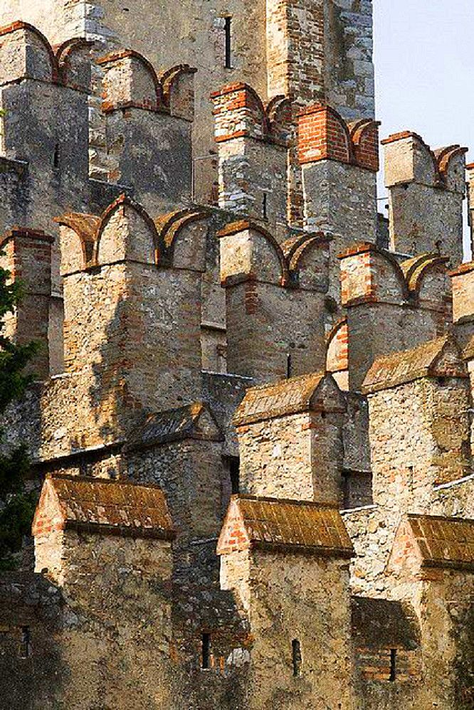 Castle Sirmione in Brescia Lombardy / Sirmione is a comune in the province of Brescia, in Lombardy (northern Italy). The Scaliger Castle (13th century) is a rare example of medieval port fortification. It presents the typical Ghibelline swallowtail merlons and the curtain-walls (with three corner towers) in pebbles alternating with two horizontal bands of brick courses.
