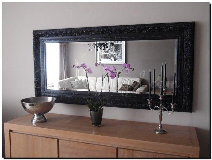Een zwarte barok spiegel boven een dressoir. Formaat spiegel 194 x 94 cm.