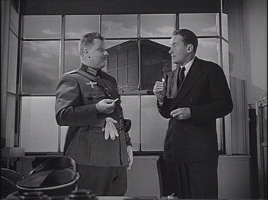 Walter Stezak and George Sanders in This Land Is Mine (1943) Mr Lambert  tells Commandant von Keller that Paul Martin is the saboteur.