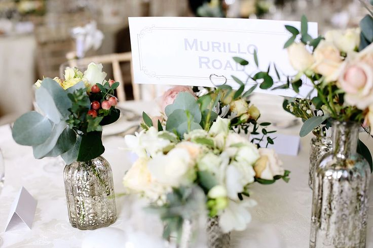 Mercury silver centrepieces. Mixed, eclectic vases of roses and eucalyptus