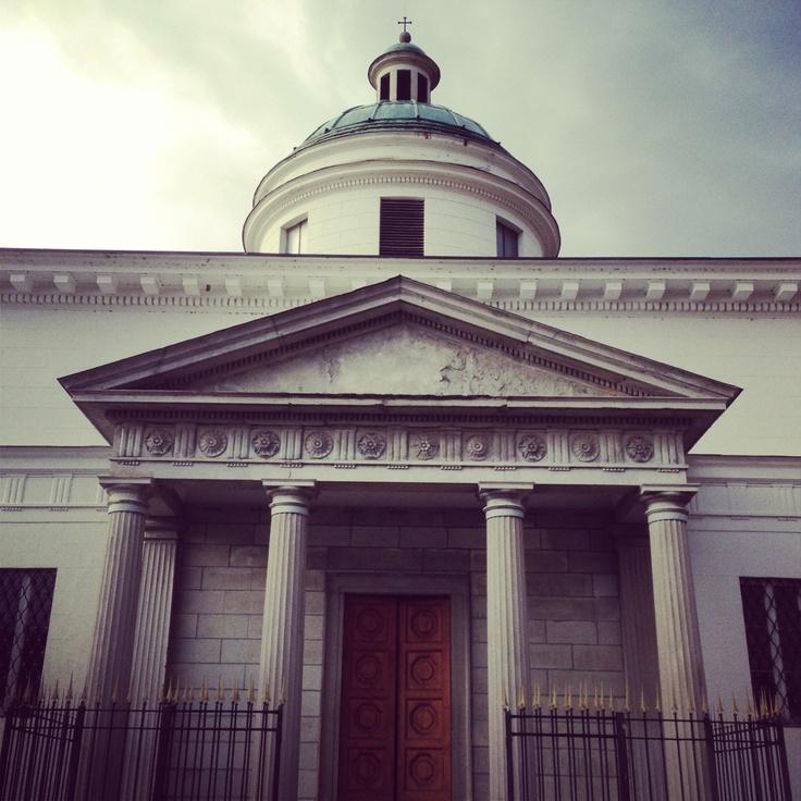 La Cappella (E) All'estremità sud del giardino, affacciata sulla piazzetta e il porticciolo di Loppia, si erge la cappella-oratorio che è parte integrante del complesso di villa Melzi. Rispecchia la consuetudine delle famiglie aristocratiche di destinare una costruzione nei giardini a spazio di culto e di sepoltura, poiché sovente chi soggiornava nelle amene località di villa, desiderava anche stabilirvi l'ultima dimora. L'edificio fu terminato nel 1818, due anni dopo la morte del I duca di…