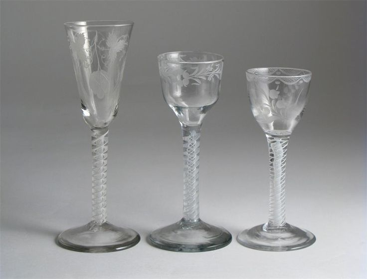 Two wine glasses and an ale glass 2nd half 18th century, the ale typically engraved with hops and barley, the wines with flowers, all raised on multiple series opaque twist stems, 17.5cm max. (3)