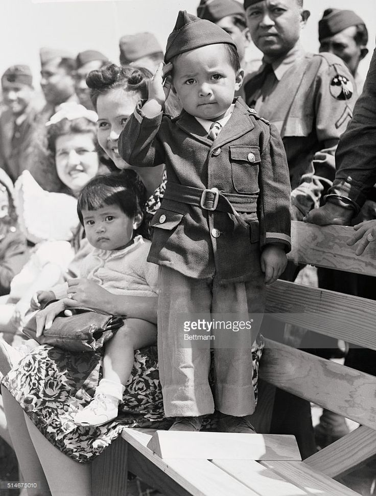 Filipino Warrior, some day. Basil Punsalan, Jr., whose Filipino daddy is a fighting West Point graduate and whose direct ancestor is Lakan Dula, famous war lord of the Philippines, renders a snappy salute as 4,500bolo knives are presented by the Los Angeles Chamber of Commerce to Filipino Fighters for Uncle Sam at Camp Cooke, CA. Two-and-a-half year old Basil was born in Boston. His father graduated from West Point in 1936, holds a degree in engineering from MIT abd is company commander of…