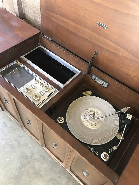 Measures 62 L 18 W 28 H - made by Zenith - vintage from 1960s - radio works - record player needs servicing - wood slat speaker covers - all original components - opens from top - small area for record storage - great condition This Zenith stereo credenza has a functioning radio that
