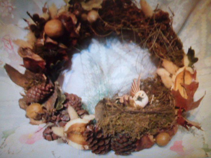 Rosca decorativa con motivo artesanal. Flores de pino, bellotas, nueces, cítricos desecados naturalmente y hojas conservadas. Un nido natural y un pajarito realístico modelado a mano, dan el detalle.