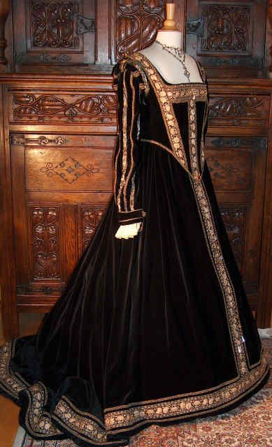 This gown, was custom-made from an original model from Eleanor of Toledo, wife of Cosimos I de Medici from1562. The full flow of this gown in black velvet as well as its optical division through the use of luxuriant wide brocade braids and gold lacings, true to the geometrical, ideally proportioned triangular forms of the Renaissance, lend this gown its majestic austerity. It is consequently complimented by a hairstyle with a centre-parting and a simple hair-net.