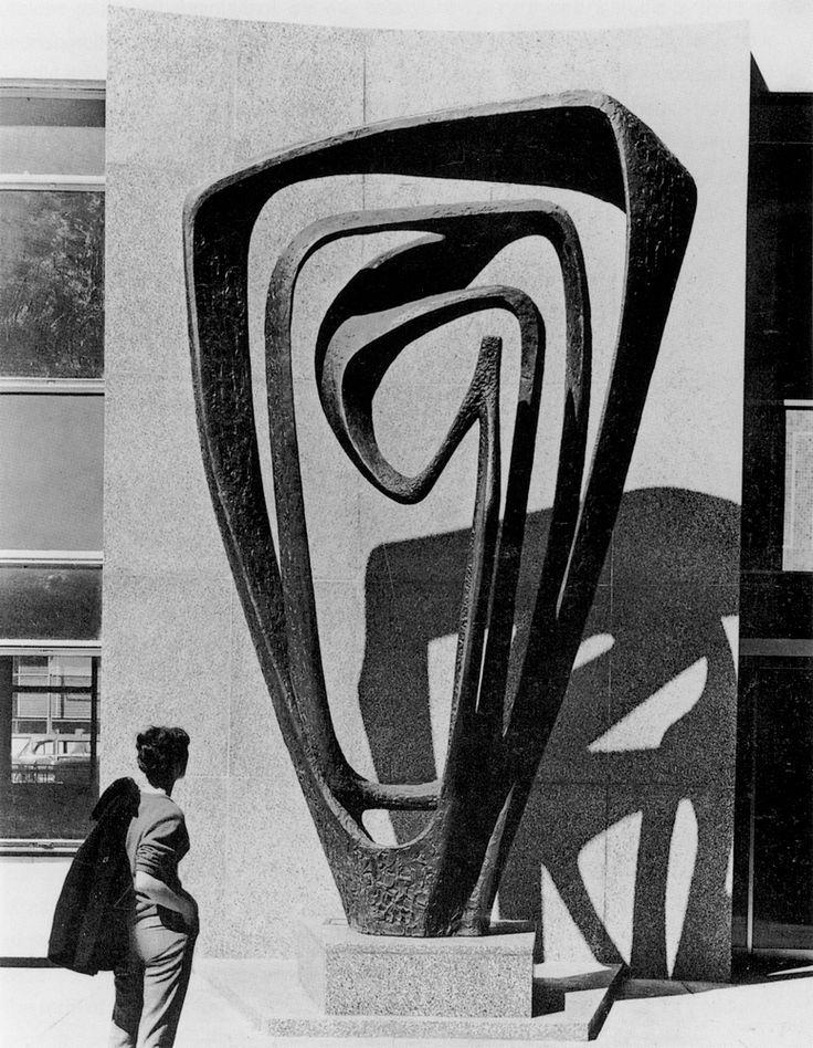 Titel: Meridian  Jaar: 1958-60  Kunstenares: Barbara Hepworth  Kunststroming: Modernisme  Het beeldhouwwerk is gemaakt van brons en heeft een lichte structuur. Het kunstwerk bestaat uit vloeiende stroken die elk een looping maken. De abstracte en vloeiende vorm sprak me erg aan. Het kunstwerk is erg groot en door de invalshoek van de zon ontstaat er een schaduw van het kunstwerk op de muur van het gebouw dat er achter staat.