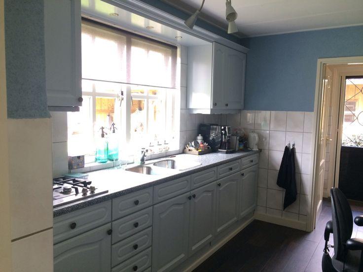 Keukenkastjes van blank eiken naar blauw-grijs en een nieuw zwart-wit blad er op. Dag-foto.