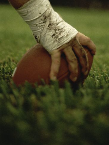 Close-up of the Hand of an American Football Player Holding a Football Photographic Print