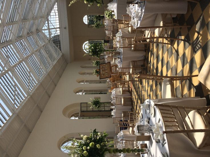 Flowers provided by www.wildorchidweddingflowers.co.uk The Orangery at Wrest Park table flowers on lime and white with apples and lime fruits