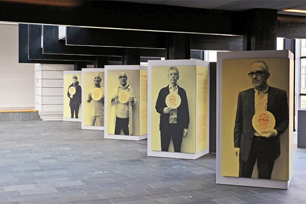 Large-scale graphics of people holding up the label identifying themselves…