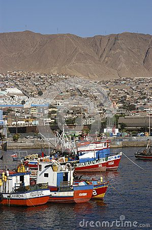 Fishing boats in the old port of Antofagasta in the background the city and its hills