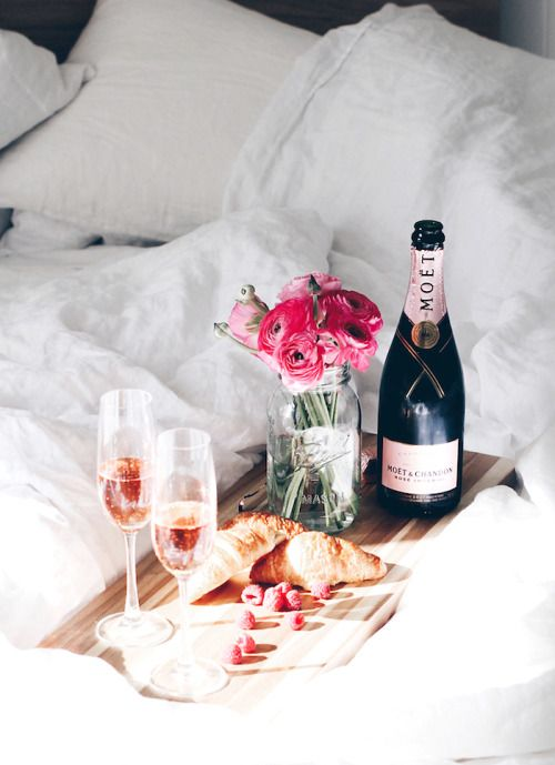 Breakfast in bed with pink champagne and ranunculus