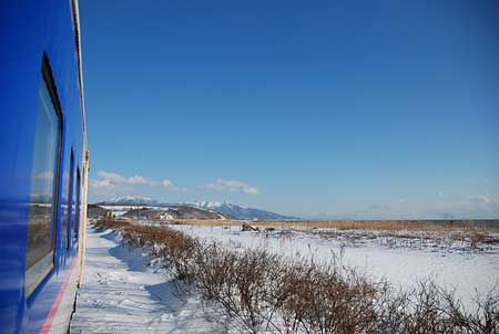 アポイ岳を遠くに認めると、列車は終着駅までの残り数駅を走り始める。原野と、その向こうに海が広がる。快晴。[2011/1 日高幌別駅付近 JR日高本線2227D様似行 車窓(キハ40形)]© 2010 風旅記(M.M.) 風旅記以外への転載はできません...