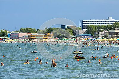 MAMAIA, ROMANIA - AUGUST 5, 2011: People enjoying a swim in the Black Sea waters and resting on the beach in Mamaia summer resort, Romania. Mamaia is the biggest seaside resort in Romania, a narrow sand bar of 250-350m width and 8.5km beach length in the north-east of Constanta.