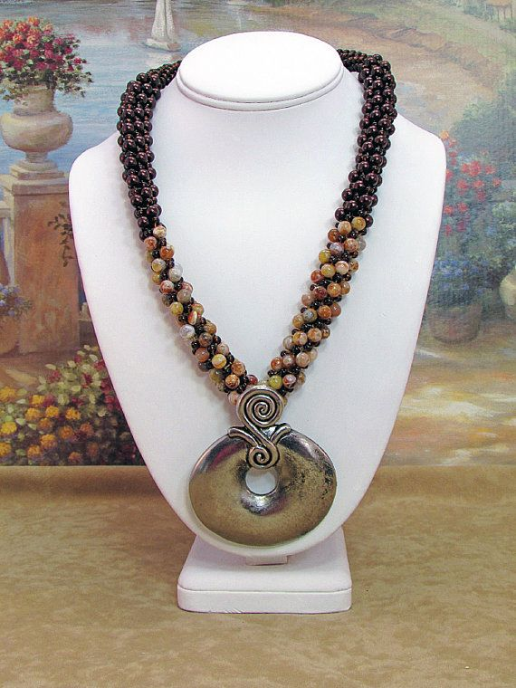 Opal and Pearl Kumihimo Braid with Pendant. Red opal and brown glass pearls were woven together with brown glass Czech beads into a Kumihimo Braid. I added a 2.5 inch gun metal pendant for drama. The necklace is finished off with silver metal bead caps and hook clasp. Approximately 20 inches.