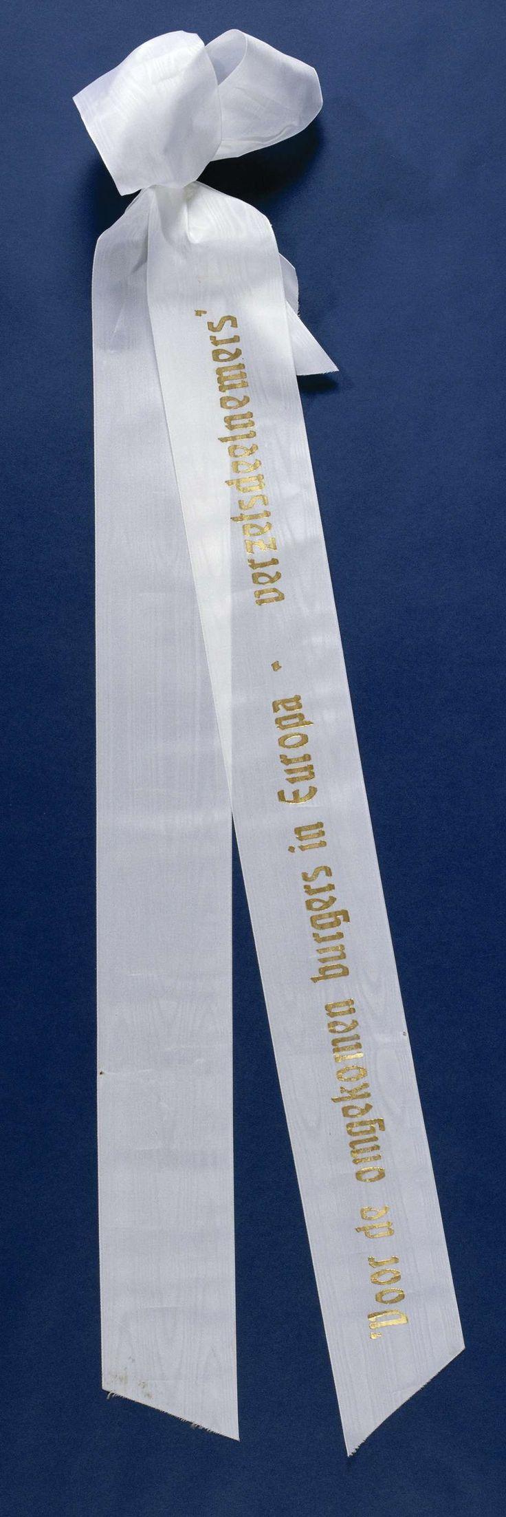 Anonymous | Lint 'Voor de omgekomen burgers in Europa - verzetsdeelnemers', Anonymous, 2000 | Twee aan elkaar gebonden witte linten, gelegd op 4 mei 2000 bij het Nationaal Monument op de Dam. Het bovenste lint is v.z.v. een gouden opdruk. Onderste lint is blanco. Linten zijn aan de uiteinden schuin afgeknipt. Aan een zijde tot strik samengebonden met ijzerdraad. IJzerdraad gebogen t.b.v. bevestiging aan krans.
