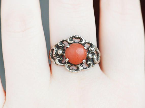 This is a rare antique design (Russian? German? Biedermeier style) natural coral and sterling silver (835 purity) ring. Unreadable makers sign. Amazingly rounded feminine forms and swirls. Very boho! The coral in the middle is natural red coral. 7.5 mm wide. Marked for 835 silver purity.