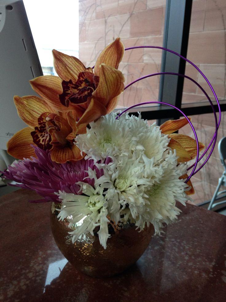 Christmas arrangement: gold orchids, white mums, purple carnations