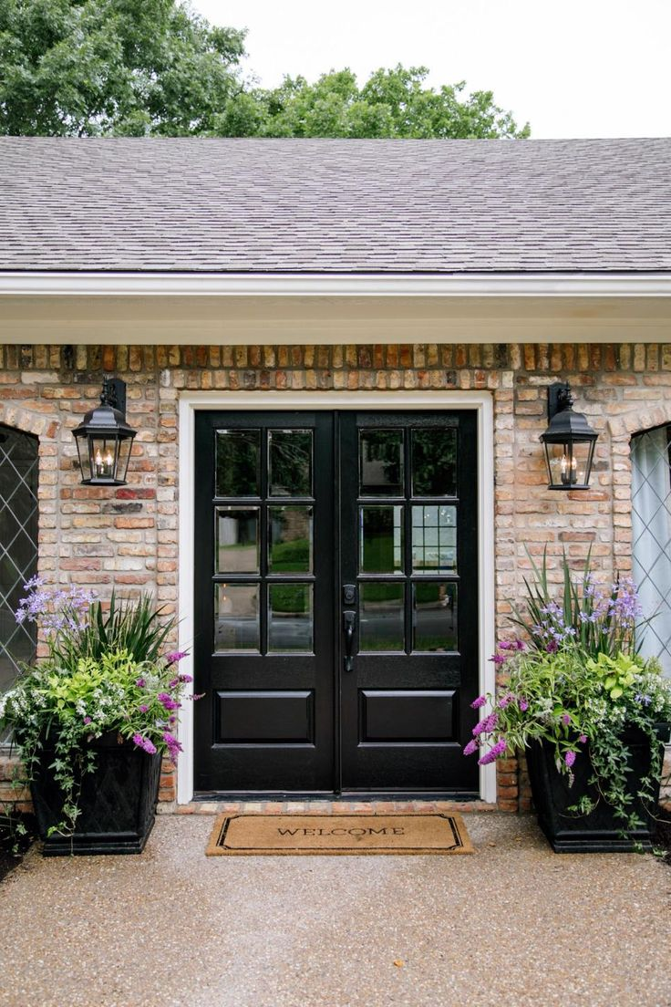 Black front door with black shutters - The New French Doors Make For A Smart New Entry That S Highlighted By Black Sconces Large Planters And Cream Paint For The Trim And Shutters