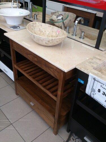 Bacha de mármol travertino, grifería hongo y vanitory madera abierto.