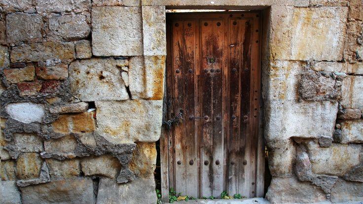 Stone wall, Salamanca Spain.  Traditional construction. Timber Door. weathered. historic.