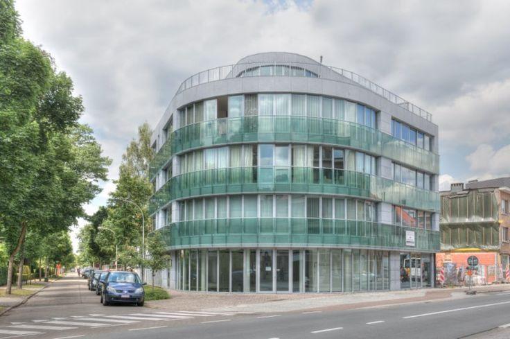 appartementsgebouw: 7 appartementen en een commercieel gelijkvloers. gevelbekleding in blauwe steen en balustrades in groen getint glas.